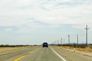 SUV noir sur route vide sous un ciel bleu nuageux