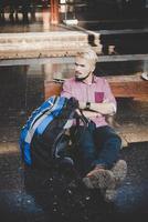Jeune homme hipster assis sur un banc en bois à la gare photo