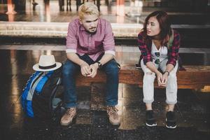 jeune couple hipster assis sur un banc en bois à la gare photo