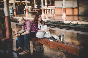 jeune couple hipster assis sur un banc en bois à la gare