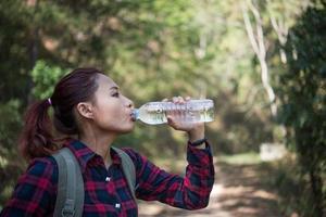touriste femme heureuse avec sac à dos eau potable dans la nature photo