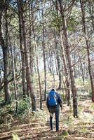 L'arrière d'un jeune homme avec sac à dos monte à la montagne photo