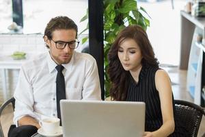 Heureux collègues réunis au café travaillant sur ordinateur portable