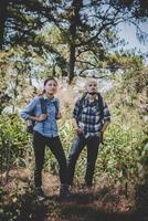 couple de randonnée à travers la forêt jusqu'au sommet de la montagne