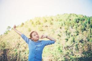 jeune femme debout regardant vers le ciel avec les mains levées photo