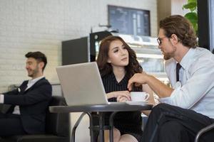 Heureux collègues réunis au café travaillant sur ordinateur portable photo