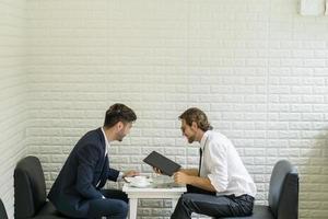 jeune homme d'affaires parlant avec un collègue dans un salon d'affaires moderne