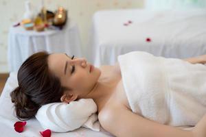 belle femme souriante avec des fleurs au repos dans le spa avant le massage photo