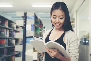 jeune étudiant asiatique lisant dans la bibliothèque photo