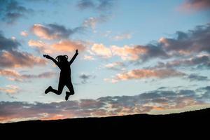 silhouette d'une jeune femme heureuse contre beau coucher de soleil