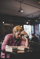 Hipster barbu livre de lecture au café. photo