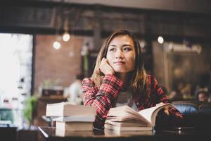 adolescent hipster assis et lisant un livre dans un café