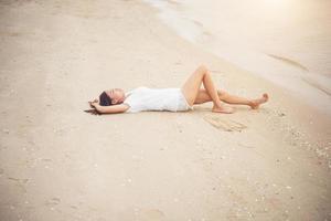 jeune femme assise sur la plage photo