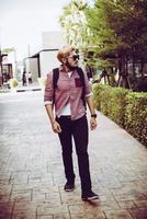 Portrait d'un bel homme hipster en jeans et lunettes de soleil à pied