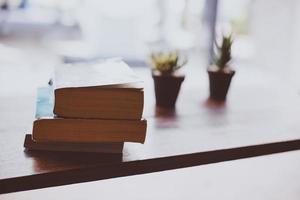 Fleur de cactus avec une pile de livres sur table en bois photo