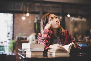 adolescent femme hipster assis profiter de la lecture du livre au café.