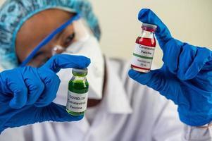 un scientifique portant un masque et des gants porte des flacons contenant des vaccins pour se protéger contre le covid-19 photo