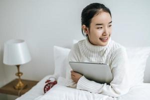 une jeune femme assise sur son lit tenant un ordinateur portable photo