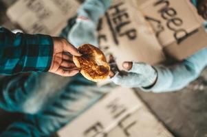 Mendiant sous le pont avec des panneaux d'aide en carton acceptant le pain
