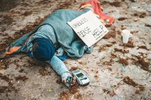 mendiant dort dans la rue avec machine à carte de crédit photo