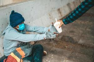 mendiant assis sous le viaduc et acceptant les nouilles de quelqu'un photo