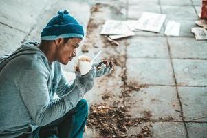 mendier sous le pont avec une tasse contenant des pièces et des nouilles instantanées photo