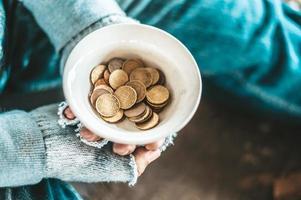 mendiant assis sous un pont avec une tasse d'argent photo
