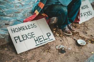 un homme est assis en train de mendier avec des sans-abri s'il vous plaît message d'aide photo