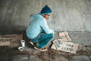 Mendiant assis sous un pont avec des panneaux en carton pour obtenir de l'aide