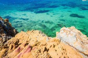 île tropicale rock sur la plage avec de l'eau vert bleu clair photo
