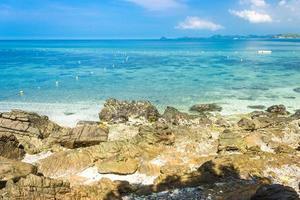 île tropicale rock sur la plage avec de l'eau bleu clair et ciel bleu nuageux photo