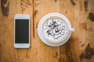 Une tasse de café et de smartphone sur une table en bois au café photo