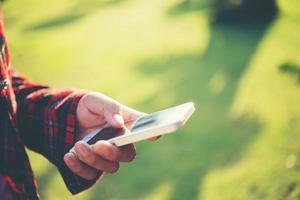 jeune femme à l'aide d'un smartphone à l'extérieur dans un parc