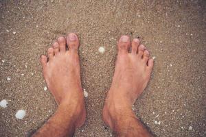 pieds du jeune homme sur la plage photo