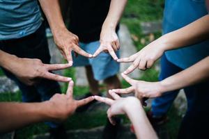 des amis forment une étoile ensemble avec les doigts photo