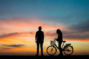 silhouette de jeune couple ensemble pendant le coucher du soleil photo