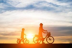 mère avec son enfant à vélo au coucher du soleil photo