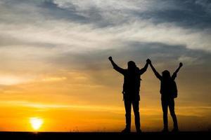 silhouettes de deux randonneurs avec des sacs à dos profitant du coucher du soleil