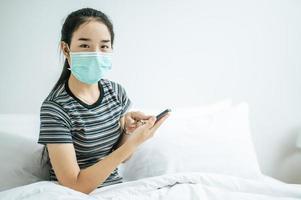 fille portant un masque sanitaire, chemise rayée et tenant un téléphone portable