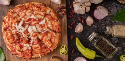 pizza sur une planche de bois avec poivrons, ail, piment et champignons shiitake