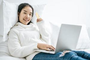 jeune femme, achats, sur, ordinateur portable, et, tenue, a, carte crédit photo