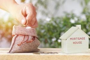 Sac de jute avec des pièces de monnaie et une maison modèle photo