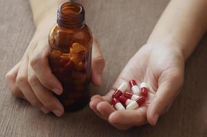 personne tenant des capsules rouges et blanches photo