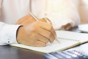 Main qui écrit dans un cahier dans un ton sombre photo
