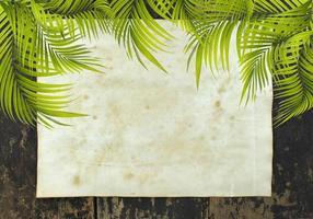 feuilles de palmier avec du papier sur une table en bois