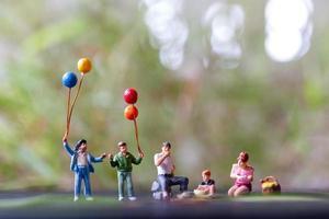 figurines miniatures d'une famille assise dans un parc