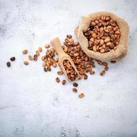 Grains de café torréfiés avec des cuillères sur fond de béton blanc