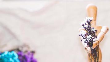 mannequin en bois tenant des fleurs photo