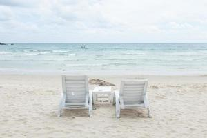 chaises longues blanches sur la plage photo