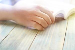 la main de la personne sur un livre photo